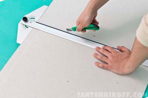 Мастер режет гипсокартон специальным ножом